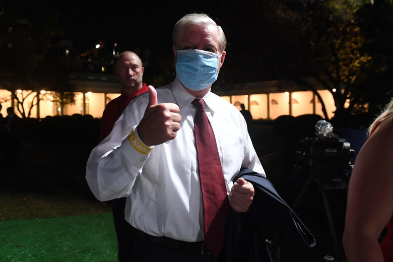 Graham, wearing a mask, gives a thumbs-up outside the White House at night