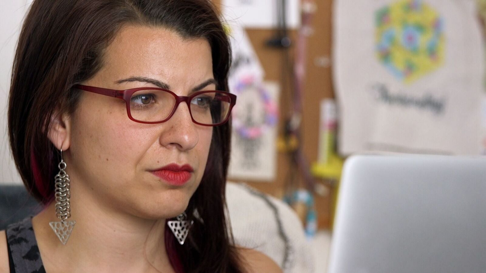 Feminist Frequency founder Anita Sarkeesian, a woman with white skin and dark brown hair wearing magenta glasses, looks at her computer screen.