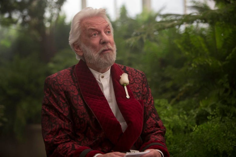Snow has white hair, a white beard, and a white rose tucked into his lapel.