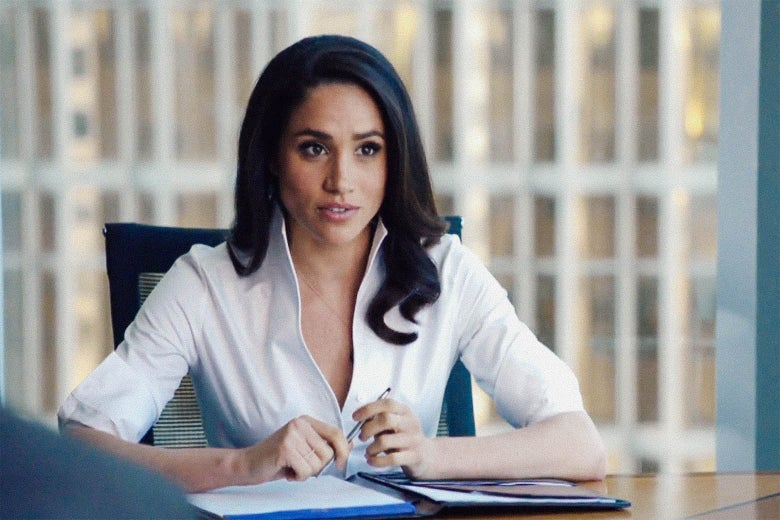 Meghan Markle sits at a desk with an open notebook in front of her. She's wearing a white blouse.