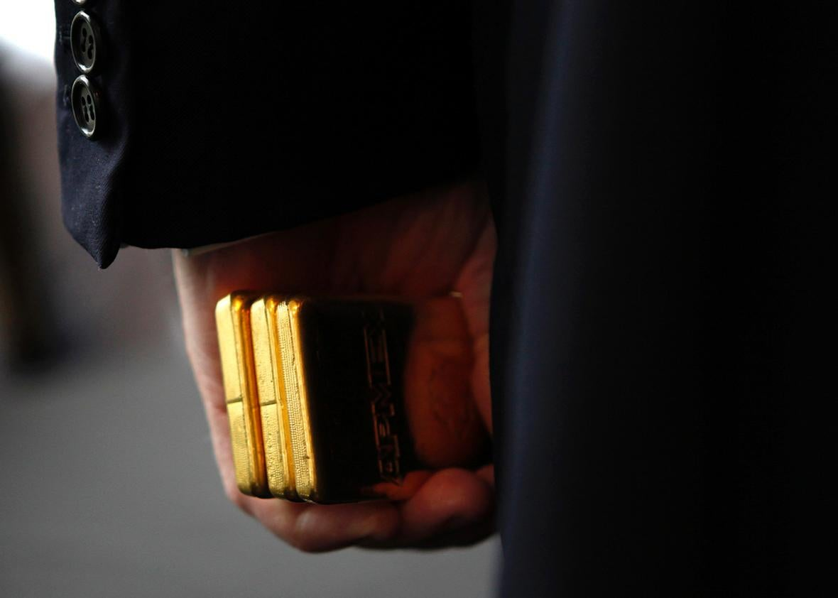 Developer Donald Trump holds three bars of Gold Bullion after accepting it as a security deposit from the American Precious Metals Exchange for a 10 year lease for APMEX on the 50th floor of 40 Wall Street in New York City, a Trump owned property, during a news conference in New York, September 15, 2011.