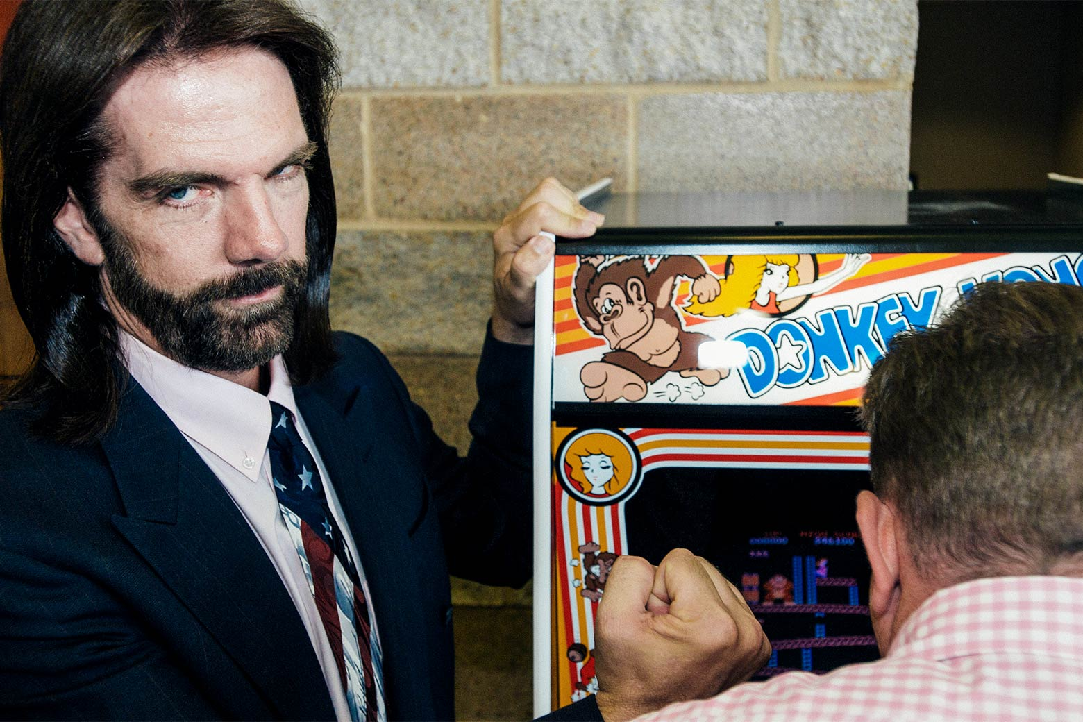 Billy Mitchell poses next to a Donkey Kong game console, 2009.