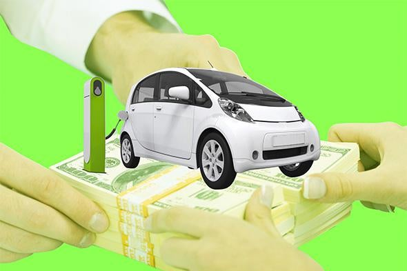A car at a charging station is seen on bundles of $100 bills being held by two pairs of hands.