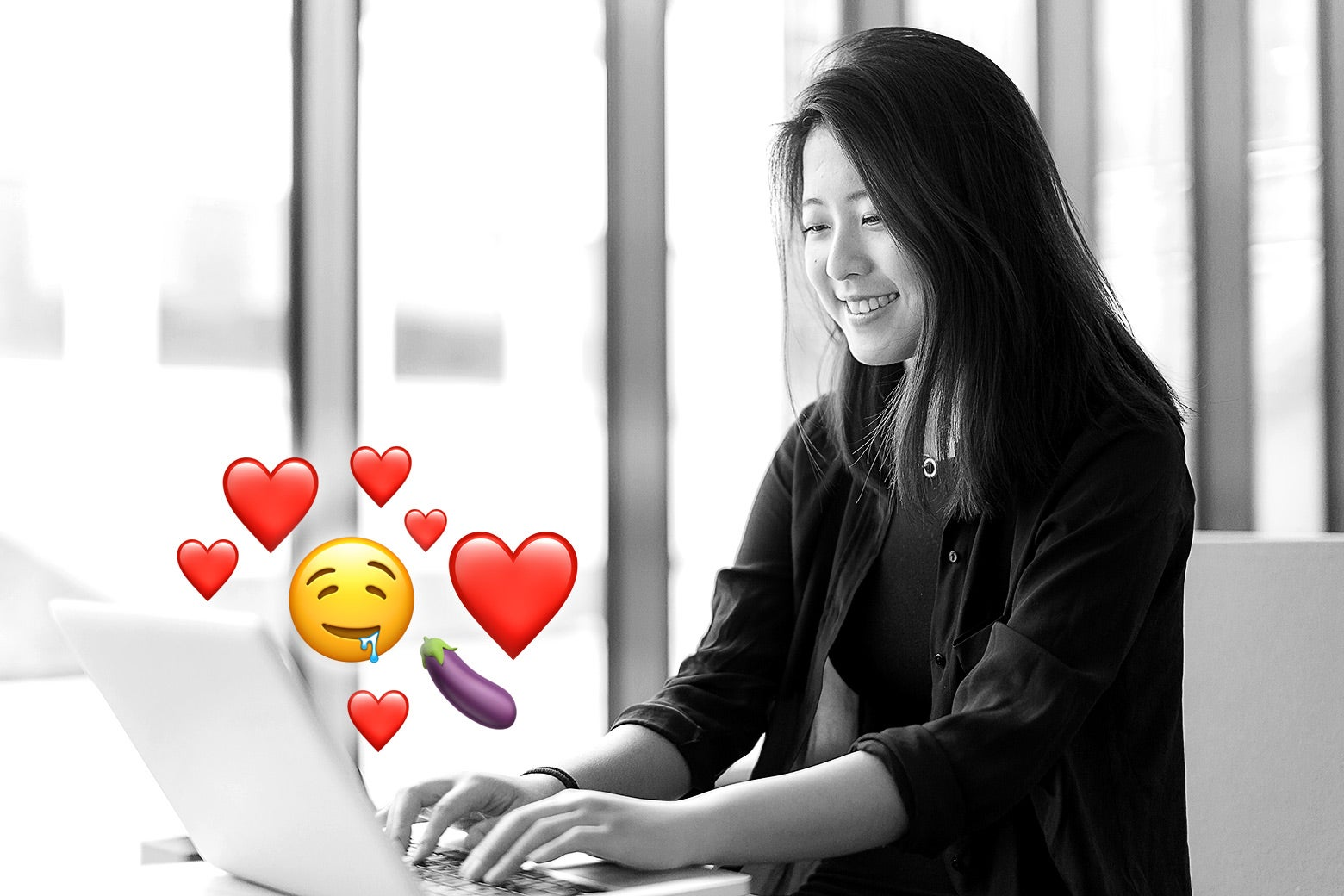 An Asian woman on her laptop typing emojis on Subtle Asian Dating.