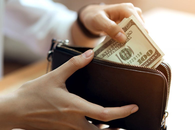 A person putting cash into a wallet.