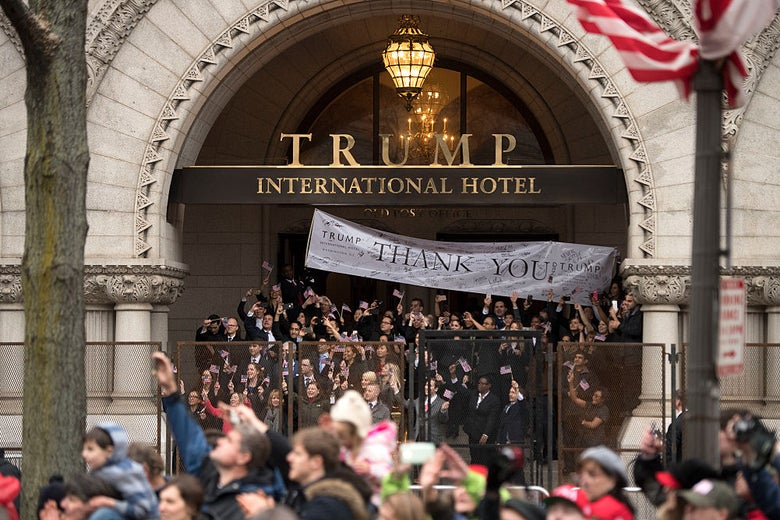 A crowd of people wearing suits stands on steps under a TRUMP INTERNATIONAL HOTEL sign as a parade passes by.
