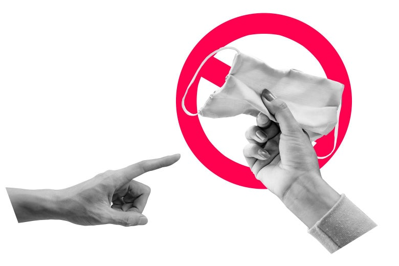 Hand pointing at a different hand holding a face mask.
