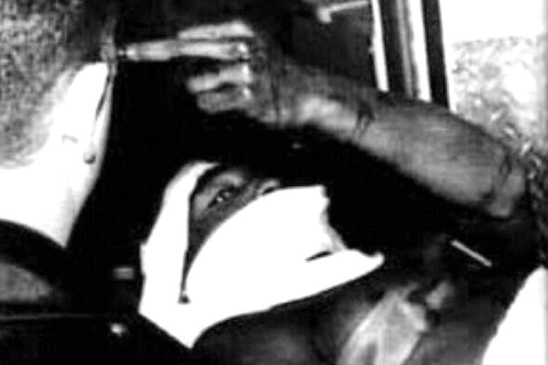 Tupac gives the middle finger while laying on a stretcher.