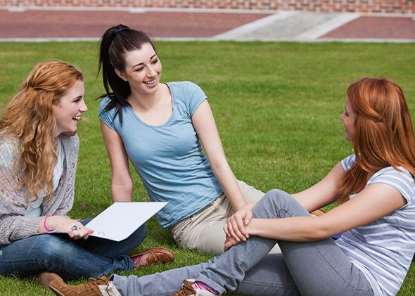 Young women sitting on a college campus lawn