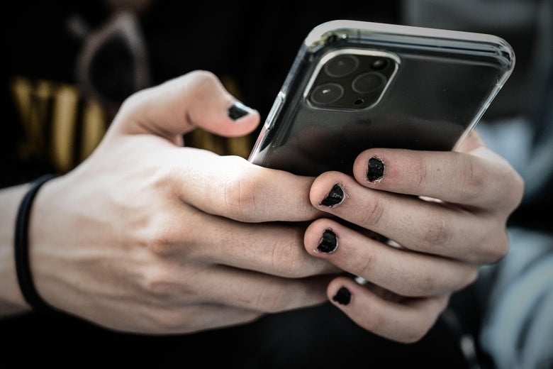 Two hands with black nail polish use an iPhone