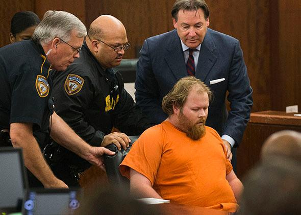 Accused mass shooter Ronald Lee Haskell is wheeled from the courtroom after collapsing during a hearing in Houston.