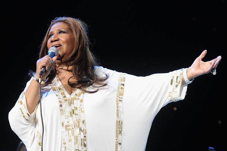 Aretha Franklin at Radio City Music Hall, arm outstretched.
