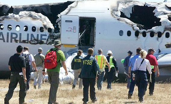 U.S. National Transportation Safety Board (NTSB) investigators work at the scene of the Asiana Airlines Flight 214 crash site at San Francisco International Airport in San Francisco, California in this handout photo released on July 7, 2013.