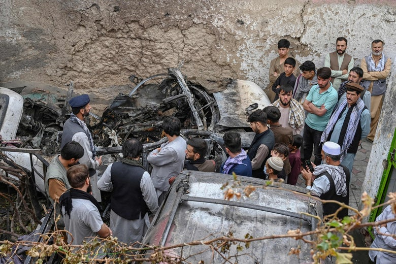 Afghan residents and family members of the victims gather next to a damaged vehicle inside a house, a day after a U.S. drone airstrike in Kabul on August 30, 2021.