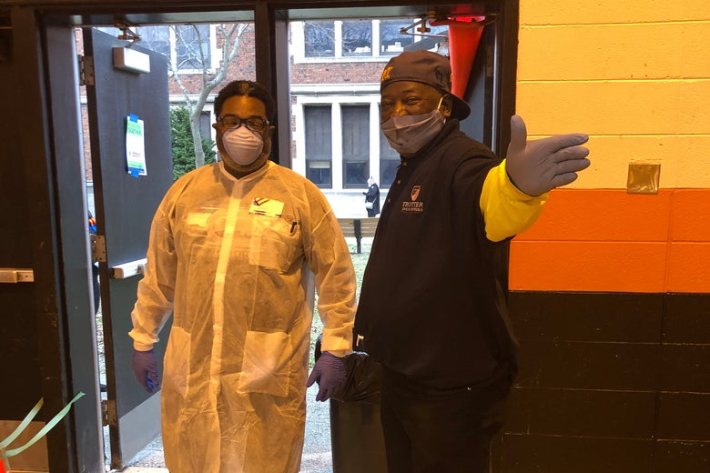 Poll workers in gowns, gloves, and masks stand by a door