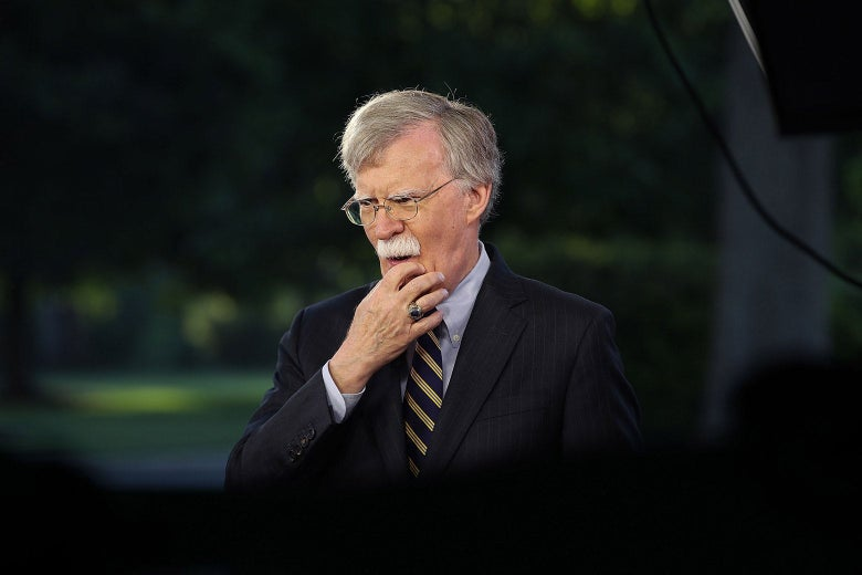 John Bolton strokes his chin while standing outside the White House.