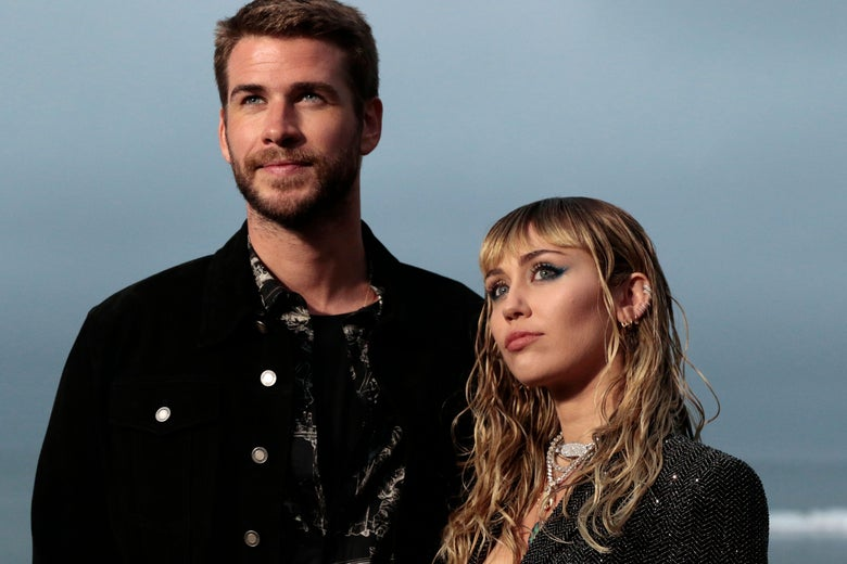 Liam Hemsworth and Miley Cyrus looking thoughtful, with an ocean in the background.