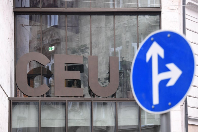 The letters CEU, for Central European University, appear on a building, next to a traffic sign with arrows pointing straight ahead and to the right.