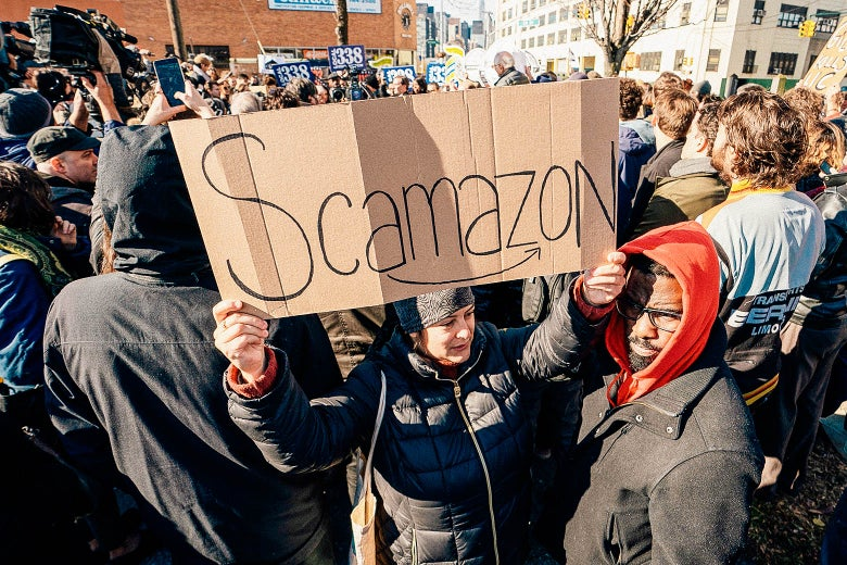 """A crowd of anti-Amazon protesters, one holding a """"Scamazon"""" sign."""