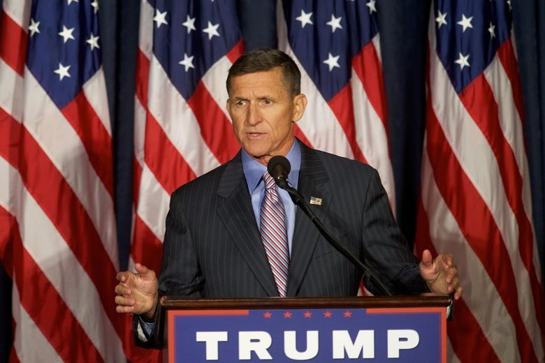Michael Flynn speaks at a podium with a Trump campaign sign on the front.