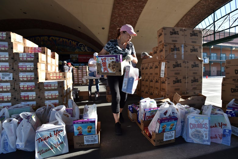 Volunteers prepare groceries to be given out at a drive-thru Three Square Food Bank emergency food distribution site at Boulder Station Hotel & Casino in response to an increase in demand amid the coronavirus pandemic on April 29, 2020 in Las Vegas, Nevada. - Three Square is currently operating dozens of emergency distribution sites at various times and dates throughout Southern Nevada to assist a growing number of people, many recently unemployed. (Photo by David Becker / AFP) (Photo by DAVID BECKER/AFP via Getty Images)