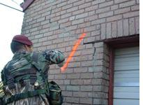 A soldier marks an empty house. Click on image to enlarge.