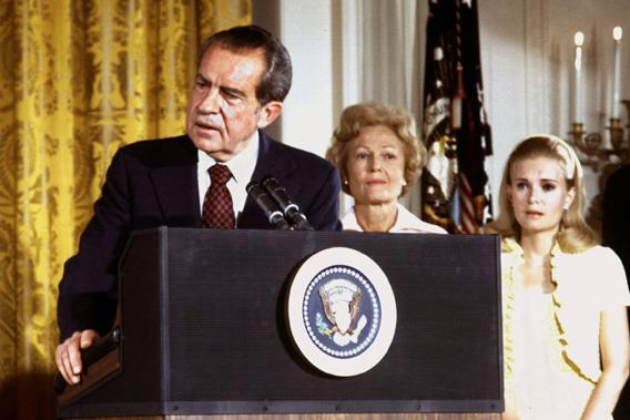 U.S. President Richard Nixon listened to by First lady Pat Nixon and daughter Tricia Nixon (R), says goodbye to family and staff in the White House East Room on August 9, 1974.