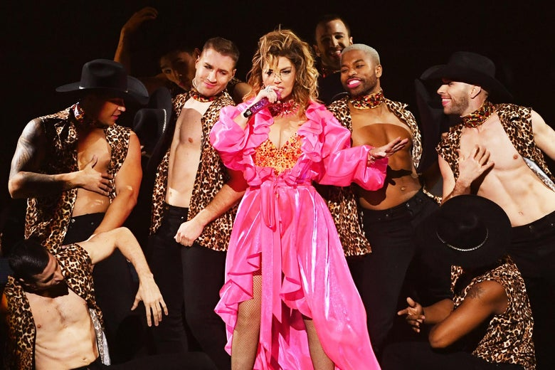 Shania Twain performing at the AMAs in a pink robe; male dancers in cheetah-print vests and cowboy hats surround her.