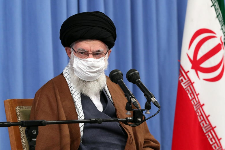 Khamenei, wearing a mask, sits at a mic with an Iranian flag to the side