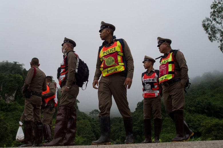 Thai police, wearing bright yellow and orange vests over their brown hats and uniforms