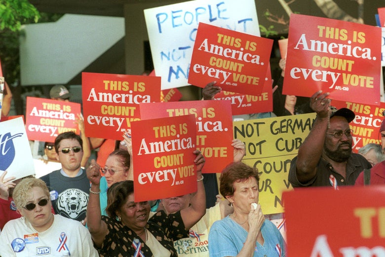 """A crowd of people holding up signs that say """"This is America. Count every vote."""""""