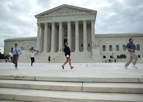 News interns run out with the ruling regarding same-sex marriage from the U.S. Supreme Court June 26, 2015 in Washington, DC.
