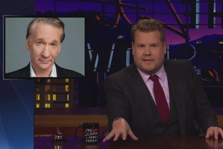 James Corden sitting at his desk on the Late Late Show, with a picture of Bill Maher behind him.