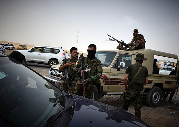 Kurdish soldiers provide security at a checkpoint as Iraqi refugee arrive fleeing from the city of Mosul. June 12, 2014.
