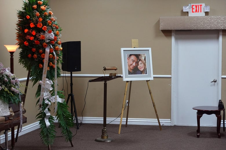 A picture of a couple beside a lectern and flowers in a room empty of people.