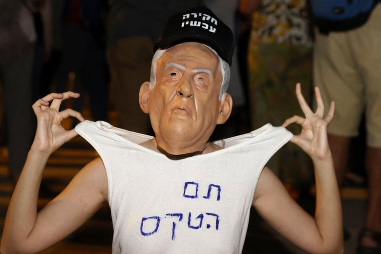 A young woman weras a mask of Benjamin Netanyahu's face, a hat, and a t-shirt with a slogan in Hebrew. She holds the t-shirt up by the shoulders with both hands.