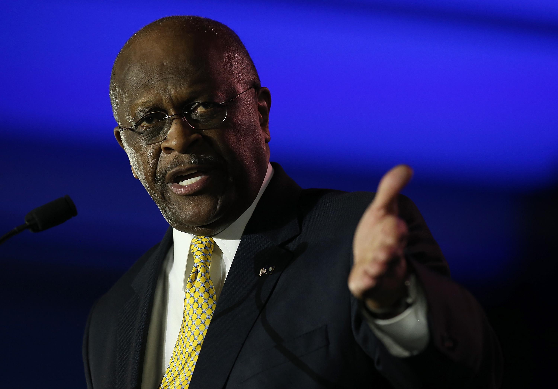 Herman Cain gesturing at a podium.