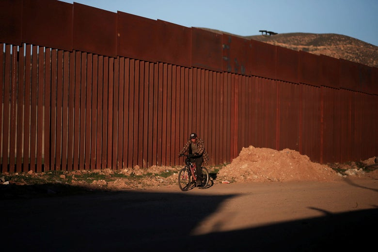 A man rides his bicycle near a border wall.
