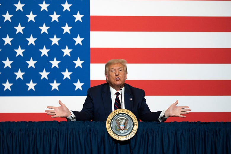 Donald Trump sits in front of an American flag backdrop, raising his hands.