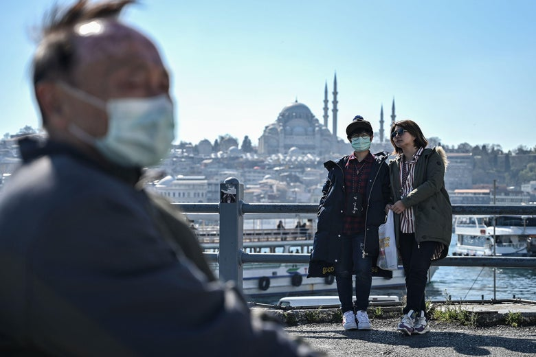 Tourists wearing face masks sit and stand on Galata Bridge.