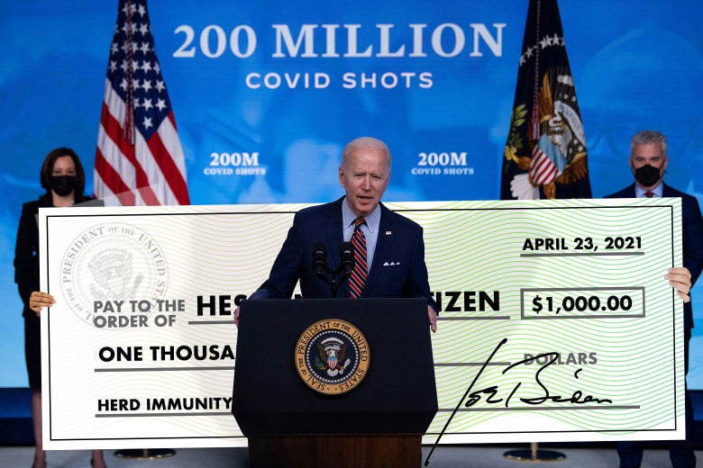 "Joe Biden speaks in front of a 200 Million Covid Shots backdrop; a large novelty check for $1,000 to ""Hesitant Citizen"" with a memo line of ""Herd Immunity"" has been photoshopped behind him."