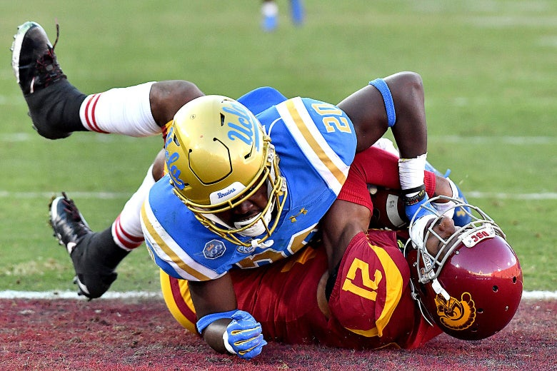 USC Trojans wide receiver Tyler Vaughns #21 catches the 49-yard pass and runs in for the touchdown as UCLA Bruins defensive back Elisha Guidry #20 defends at the Coliseum on Nov. 23, 2019 in Los Angeles.