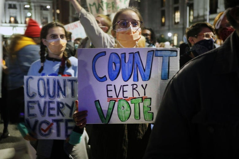 "A young woman wearing a mask stands in a crowd holding a homemade ""Count Every Vote"" sign."