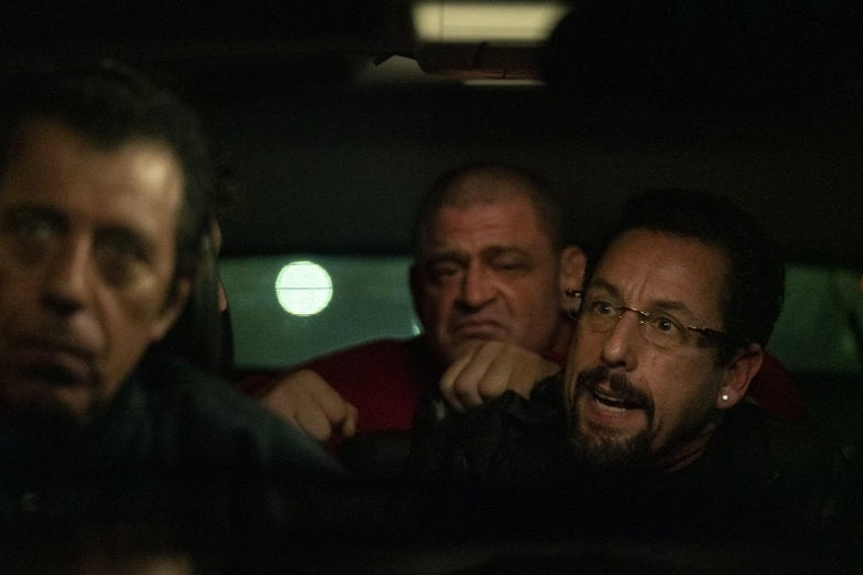 Adam Sandler in a car with two other men.