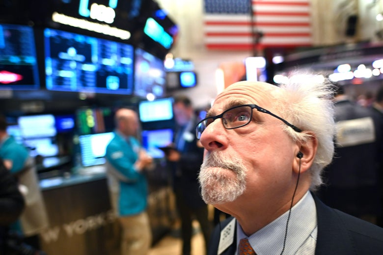A trader with Doc Brown hair stands on the floor of the NYSE, looking up nervously and clenching his teeth