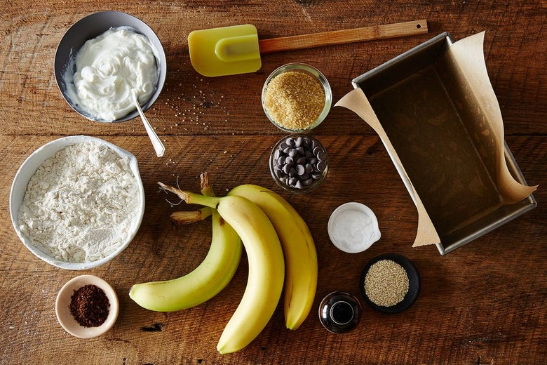 Three bananas on a wooden table. One grey bowl with white creme, one white bowl with flour, a glass bowl with chocolate chips, four more small bowls with other ingredients. A bread baking container with parchment paper.