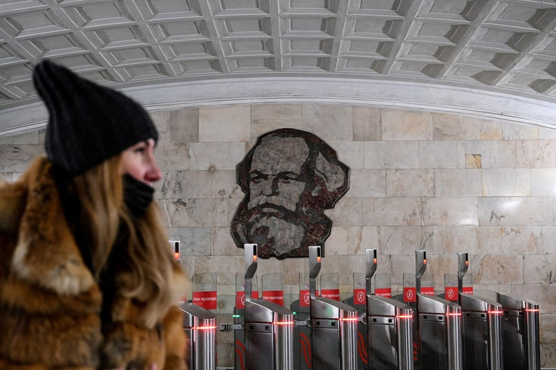 A woman wearing a face mask walks in front of an image of German philosopher and economist Karl Marx in subway in Moscow on March 12, 2021.