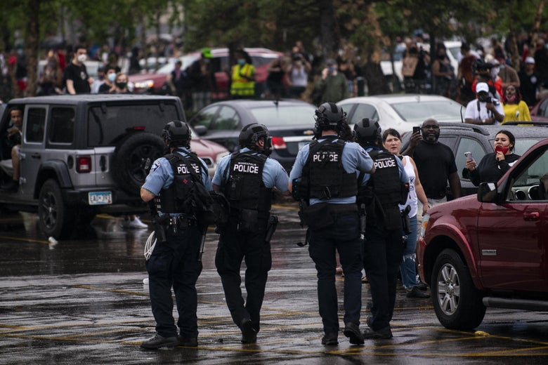 Police wearing tactical gear walk through a parking lot toward a crowd of protesters