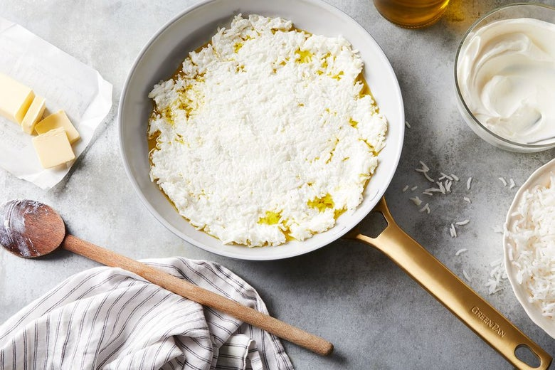 White rice and oil in a pan on a gray marble countertop, a wooden spoon, a sliced stick of butter, a striped cloth, and a bowl of cream sit nearby.