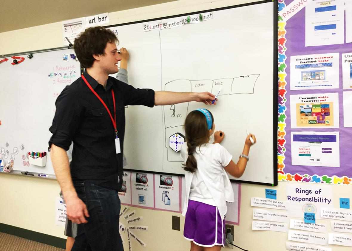 Emily Harmon, a third grader at the Woodward School in Southborough, Massachusetts, puts Root the code-teaching robot through its paces, along with Raphael Cherney, research assistant for Harvard's Wyss Institute for Biologically Inspired Innovation.